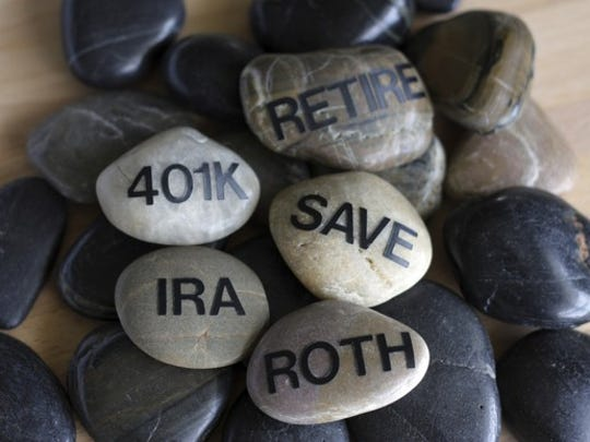 Smooth stones with words written on them such as retire, 401k, IRA, Save, and Roth.