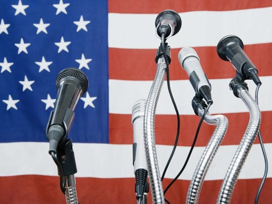 Five microphones in front of a U.S. flag.