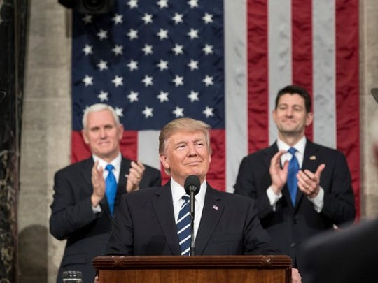 Donald Trump at a podium with Vice President Mike Pence and Speaker of the House Paul Ryan standing behind him.