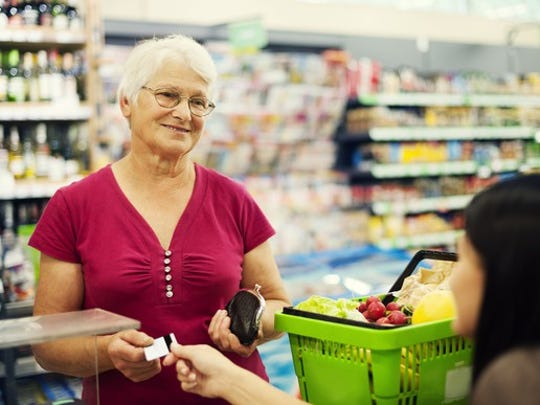 An elderly woman buying groceries.