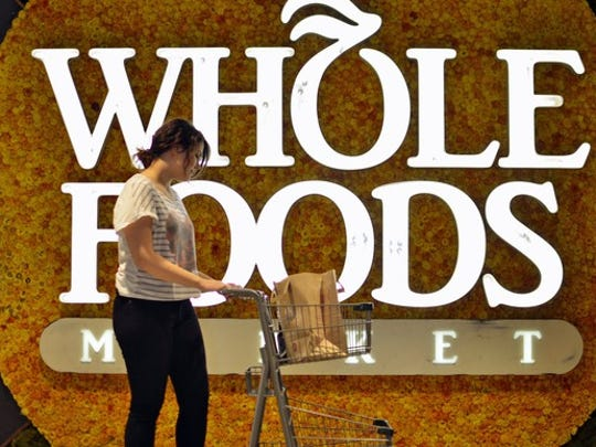 A person pushing a shopping cart in front of a Whole Foods Market sign.