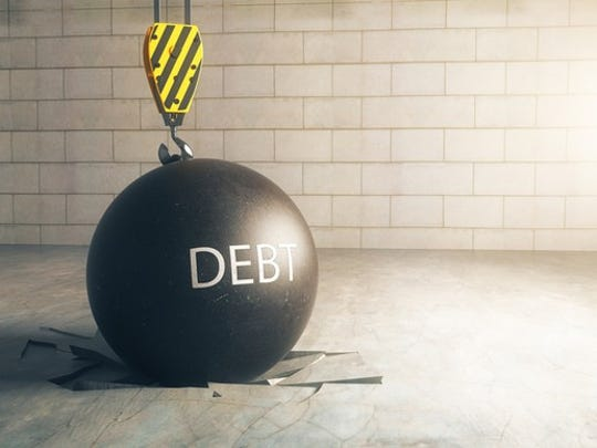 A black wrecking ball, with the word DEBT written on it, on top of a floor that it has obviously broken upon landing