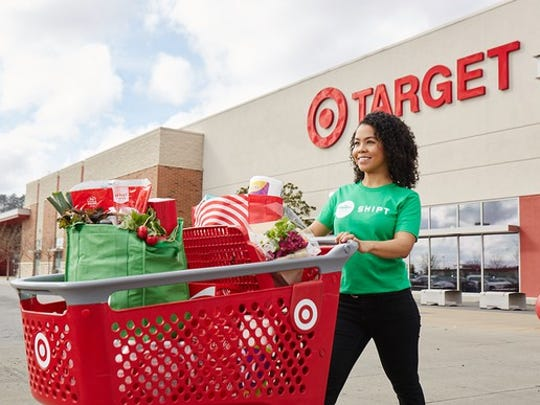 A woman wearing a Shipt shirt pushing a target shopping car outside of a store.