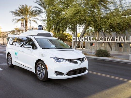 A Chrysler Pacifica Hybrid minivan with Waymo logos and visible self-driving hardware is shown on a public road in Chandler, Arizona.