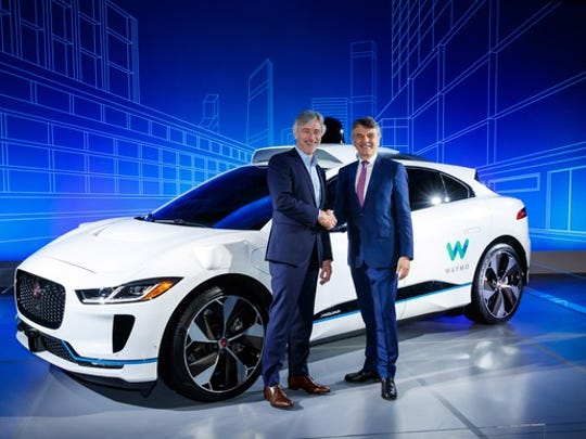 The two executives are standing in front of a white Jaguar I-Pace SUV with Waymo logos and visible self-driving sensor hardware.