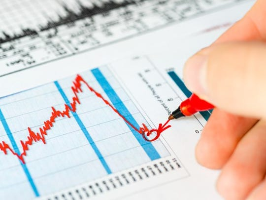A person using a pen to point to a stock market bottom on a chart.