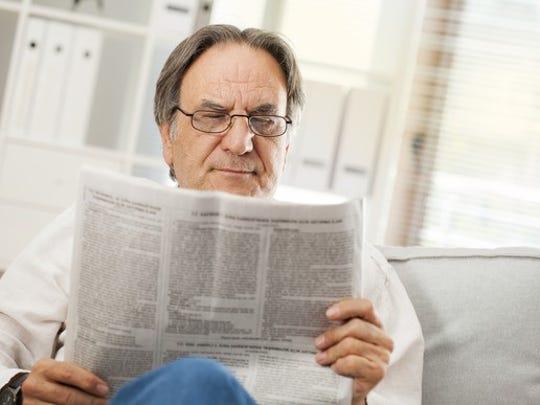 Older man reading a newspaper