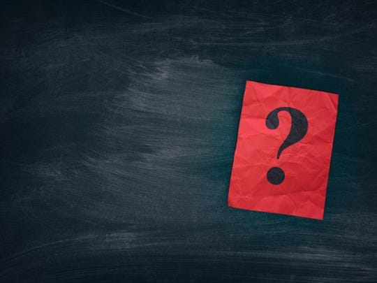 A question mark on a red piece of paper on top of a black chalkboard.