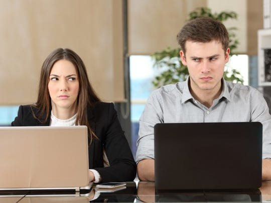 A man and a woman working at laptops cast sideways glances at each other.