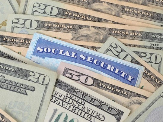 Social Security card shuffled into a spread-out pile of U.S. money.