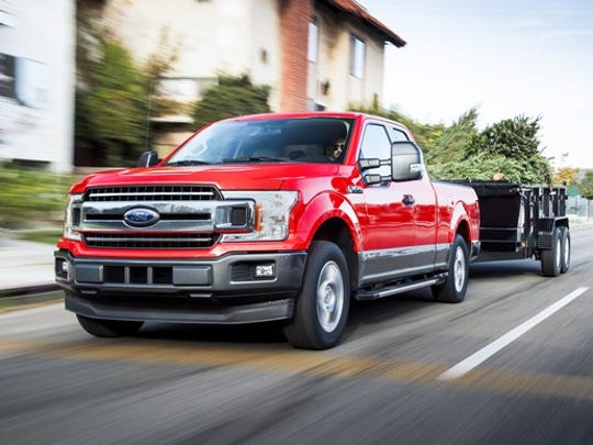 A red Ford F-150 diesel-powered pickup truck is shown pulling a trailer.