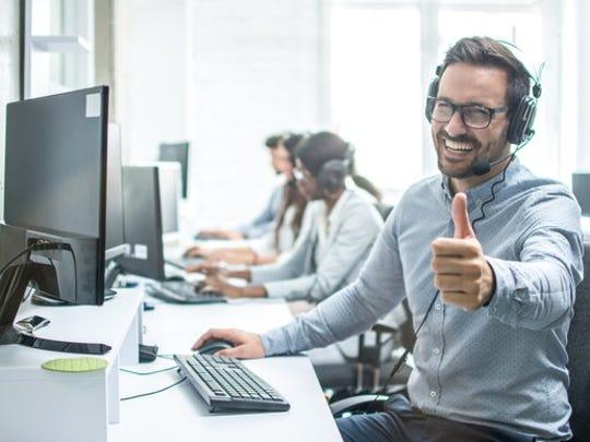 Call center representative sitting at computer, giving a thumbs-up