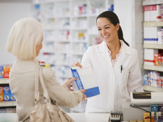 Female pharmacist hands female customer prescribed drugs