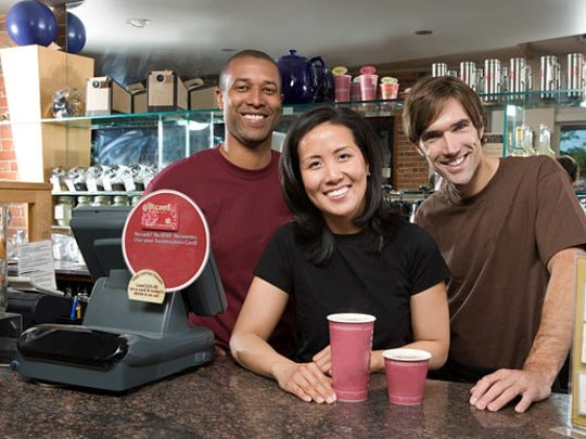 Three people behind the counter at a coffee shop.