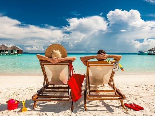 A man and a woman relax at a beach.
