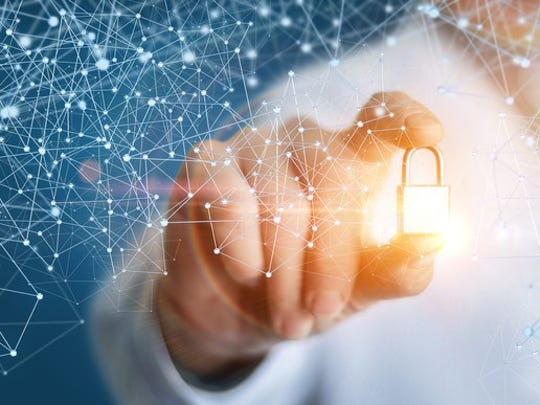 A person holding a glowing golden lock that's surrounded by latticework representative of blockchain.