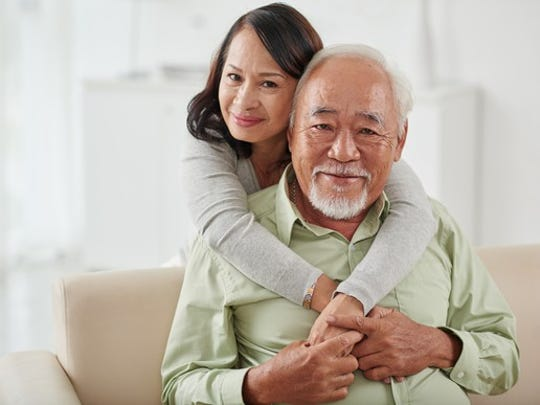An elderly couple embracing one another.