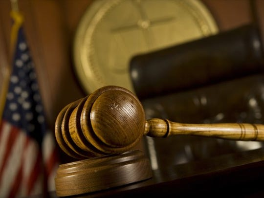 A judge's gavel and chair in the foreground of a courtroom.