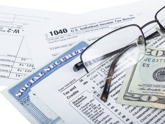 A Social Security card lying next to IRS tax form 1040, a pair of reading glasses,and a twenty-dollar bill.