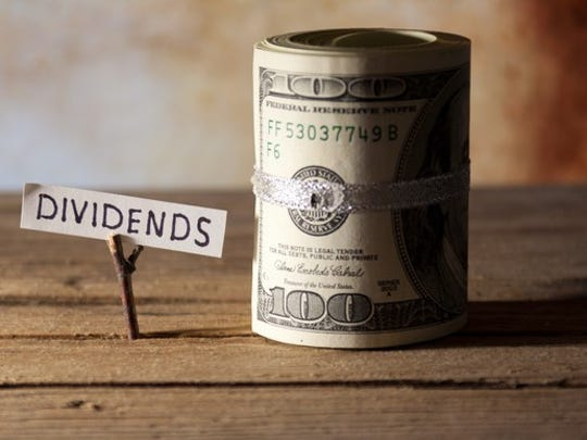 A roll of dollar bills beside a note saying dividends.