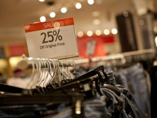 A 25%-off sign on a rack of jeans.