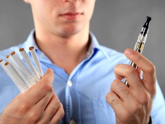 A man holding cigarettes in his right hand and an electronic cigarette in his left