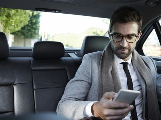 A businessman using a smartphone in the back of a Taxi cab.