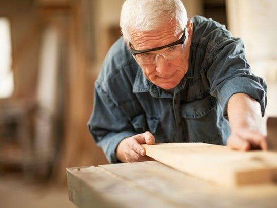 A senior man cutting lumber in a wood shop.