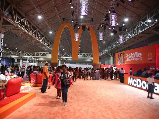 Golden arches logo hanging over convention center floor, with McDonald's booth nearby and many attendees in the hall.