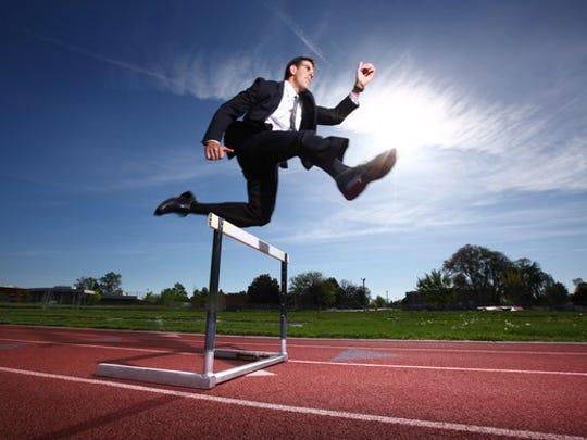 Businessman jumping a hurdle.