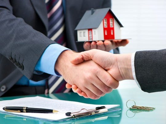 Two businessmen shaking hands, with one holding a miniature house in his left hand.