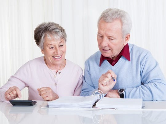 A happy senior couple examining their finances.