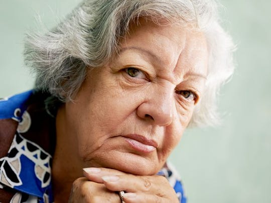 A senior woman in deep thought with her chin resting on her interlocked hands.