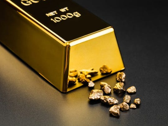 A polished gold bullion with tiny gold fragments next to it.