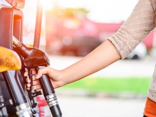 A woman grabbing the handle at a gas pump.