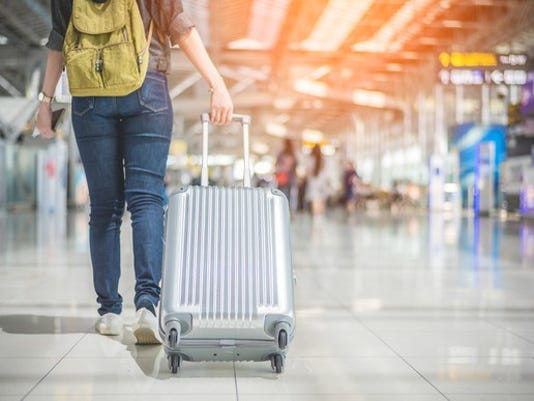 woman-pulling-suitcase-in-airport_large.jpg