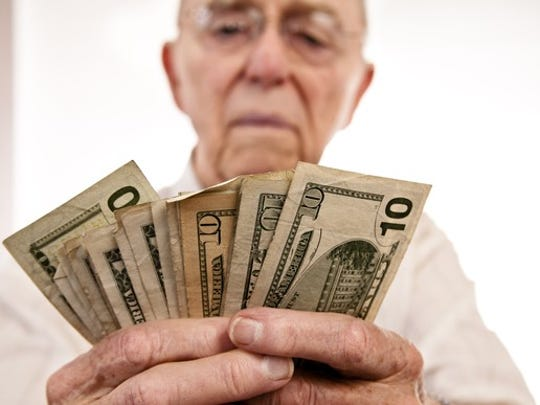 An old man counting a stack of fanned cash.