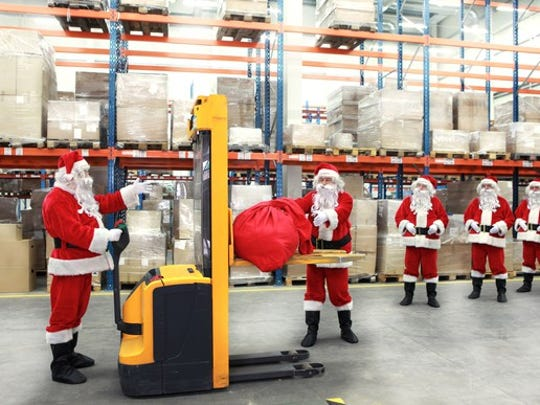 Workers dressed as Santa Claus work in a warehouse.
