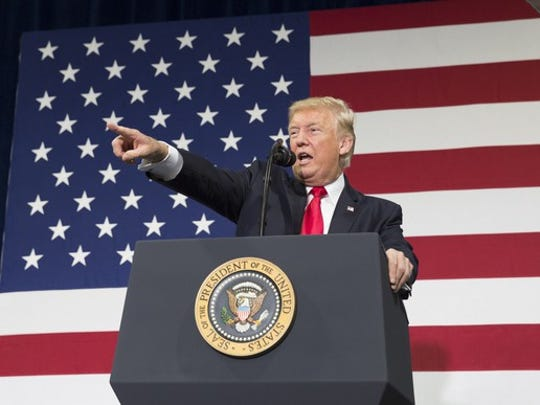 President Trump pointing to the crowd from behind the podium, with a large U.S. flag in the background.