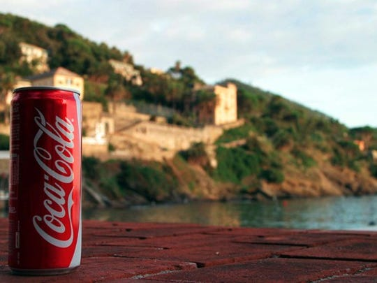 A Coca Cola red sitting on a brick walkway with a scenic view in the background.