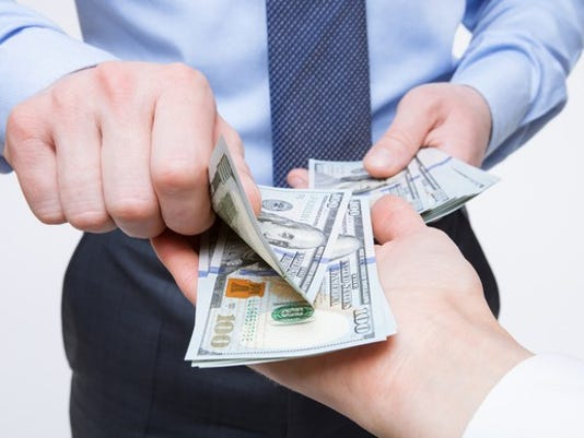 human-hands-exchanging-money-getty_large.jpg
