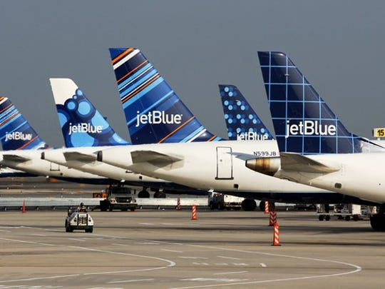 JetBlue tailfins lined up at the terminal.