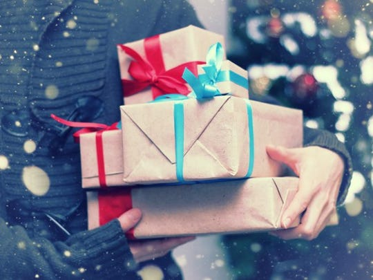 A person carries wrapped gifts.