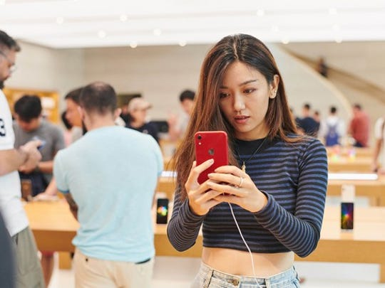 A woman looking at a red iPhone in an Apple store in Singapore.