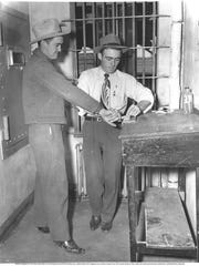 Interior: Eddy County Deputy Sheriff Bill Drake (as a joke) takes the fingerprints of Dick Floyd (also with the Sheriff's Department). Two cell doors are  visible. Circa 1951, January. Collection of Clarence Krebs