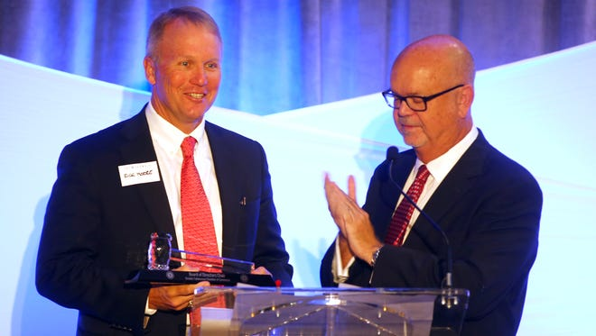 Rick Moore, left, the incoming chair of the Greater Tallahassee Chamber of Commerce, receives the gavel from Ed Murray Jr., the outgoing 2014 chair.