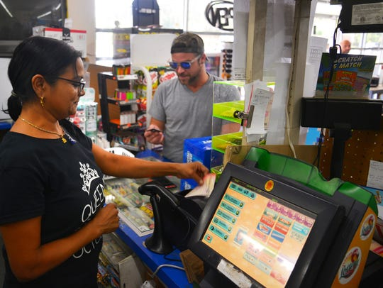 Jackie Patel rings up Aaron Fisher's two Powerball