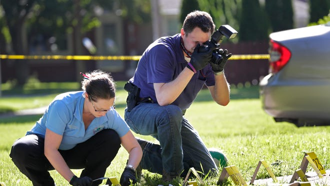 Forensic evidence specialist Larissa Asmus  and Sgt. Riddle of the Appleton Police Department investigate the scene of a homicide at 159 Foster Court Saturday, June 11, 2016, in Appleton, Wisconsin. Dan Powers/USA TODAY NETWORK-Wisconsin