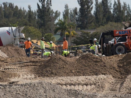 Construction crews work on a site next to Lakes Park