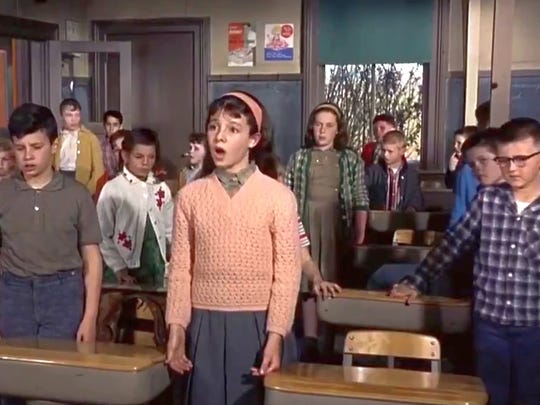 Screen shot of schoolroom scene from The Birds. Russell, right of center in yellow green checked sweater, and other kids react to an unexpected fire drill request